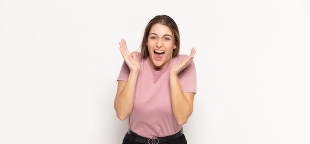 予期せぬ驚きのためにショックを受けて興奮し、笑い、驚き、そして幸せを感じている若いブロンドの女性