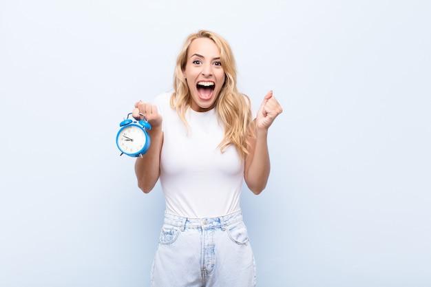 Молодая блондинка чувствует себя шокированной, взволнованной и счастливой, смеясь и празднуя успех, говоря вау! держит часы