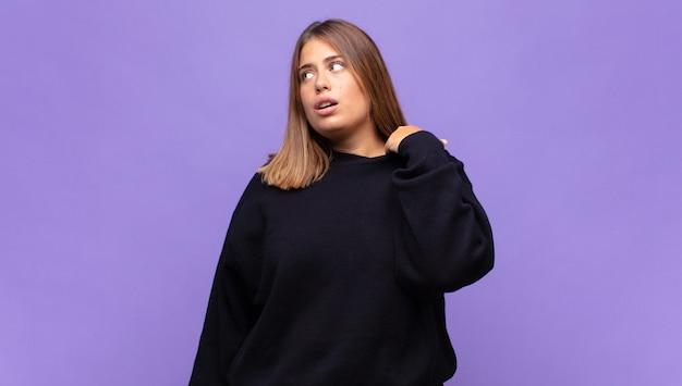 Молодая блондинка чувствует стресс, тревогу, усталость и разочарование, дергает за шею рубашки и выглядит разочарованной из-за проблемы