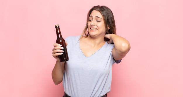 若いブロンドの女性は、ストレス、不安、疲れ、欲求不満を感じ、シャツの首を引っ張って、問題で欲求不満に見える