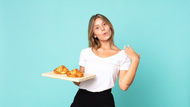 Young blonde woman feeling stressed, anxious, tired and frustrated and holding a croissant tray