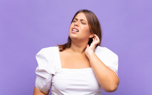 若いブロンドの女性は、ストレス、欲求不満、疲れを感じ、痛みを伴う首をこすり、心配し、問題を抱えた表情で
