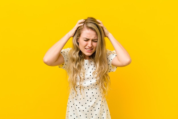 Young blonde woman feeling stressed and frustrated, raising hands to head, feeling tired, unhappy and with migraine over yellow wall
