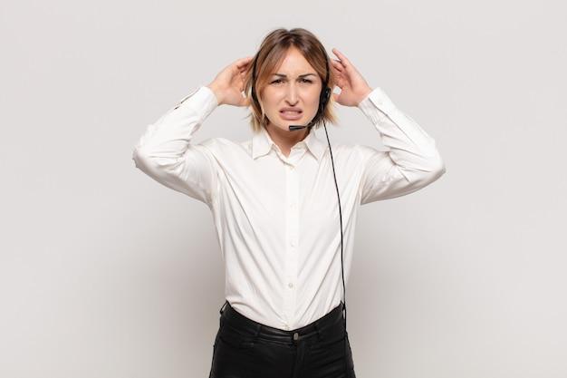 若いブロンドの女性は、頭に手を置いて、ストレス、心配、不安、または恐怖を感じ、誤ってパニックに陥る