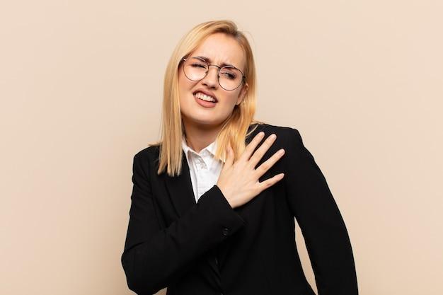 Молодая блондинка чувствует усталость, стресс, тревогу, разочарование и депрессию, страдает от боли в спине или шее