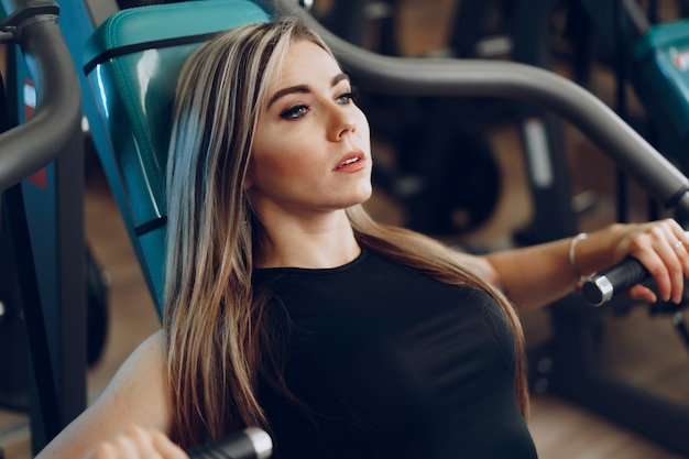 Молодая блондинка фитнес-тренер делает тренировку рук