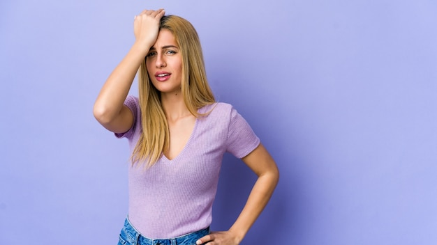 Young blonde woman forgetting something, slapping forehead with palm and closing eyes.