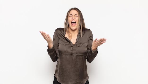 若いブロンドの女性は猛烈に叫び、ストレスを感じ、空中で手を上げてイライラし、なぜ私が