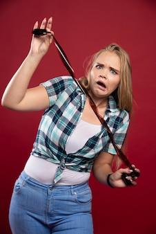 若いブロンドの女性は、ポラロイドフィルムをチェックしている間、混乱して失望します。