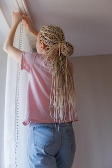 창이에 커튼을 거는 젊은 금발 여자