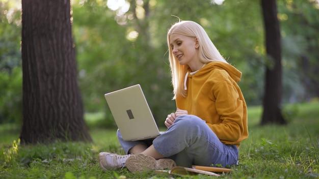 Молодая блондинка с удовольствием разговаривает по видеозвонку, используя ноутбук на зеленой траве. связь на удалении за городом. поход. 4k uhd
