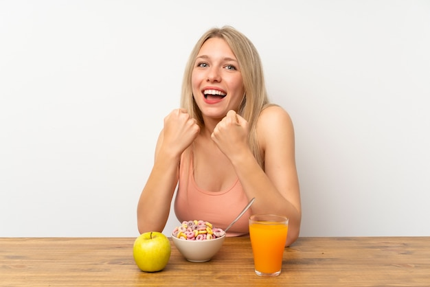 Young blonde woman having breakfast celebrating a victory