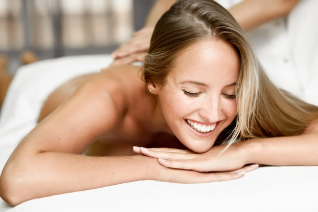 Молодая блондинка женщина, массаж и улыбка в спа