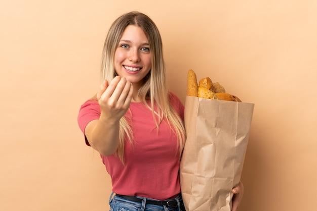 Молодая блондинка держит сумку, полную хлеба, изолированную на бежевой стене, приглашая приехать