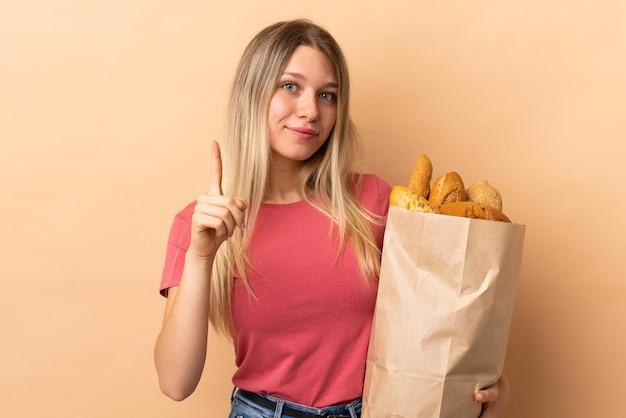 검지 손가락으로 좋은 아이디어를 가리키는 베이지 색 벽에 고립 된 빵의 전체 가방을 들고 젊은 금발의 여자