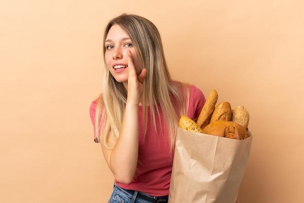 何かをささやくベージュの壁に分離されたパンの完全な袋を保持している若いブロンドの女性