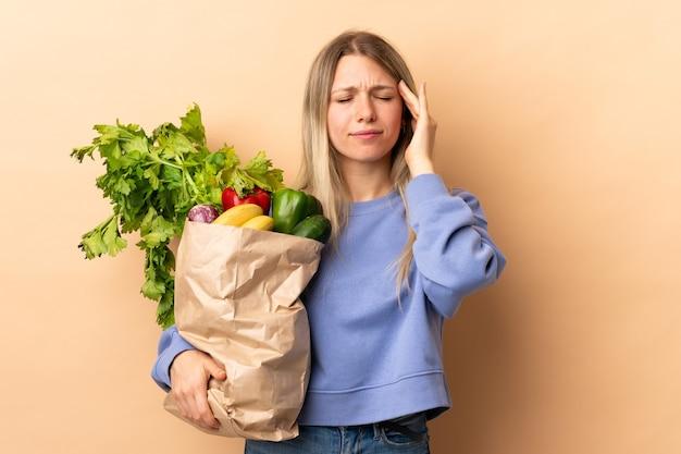 孤立した壁に野菜でいっぱいのバッグを持っている若いブロンドの女性は不幸で何かに不満を持っています