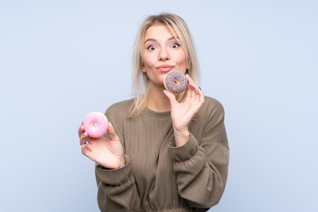 Молодая блондинка держит пончик