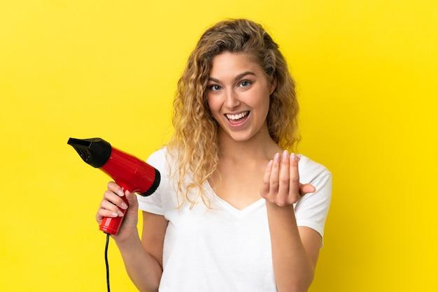 Молодая блондинка женщина держит фен, изолированные на желтом фоне, приглашая прийти с рукой. счастлив что ты пришел
