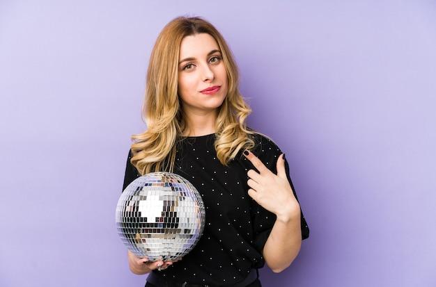 Молодая блондинка женщина, держащая мяч ночной вечеринки, изолировала указывая пальцем на вас, как будто приглашая подойти ближе.