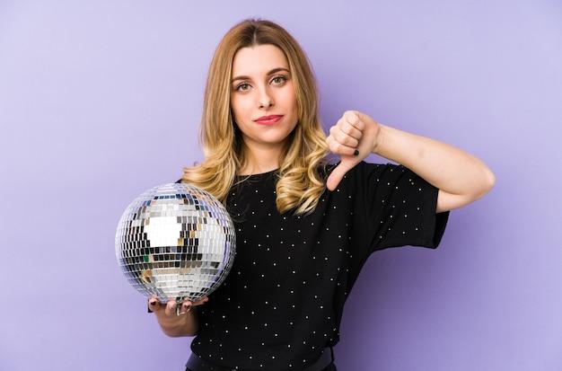 嫌いなジェスチャーを示して、親指を下に向けて孤立した夜のパーティーボールを保持している若いブロンドの女性。不一致の概念。