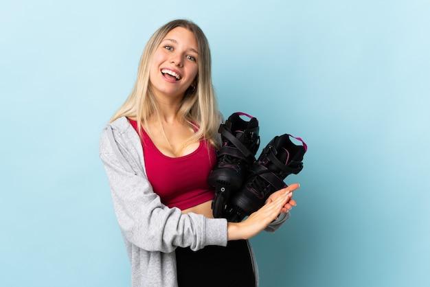 ピンクの壁に孤立したローラースケートを保持している若いブロンドの女性は拍手