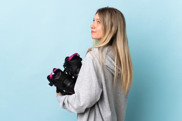 ピンクの壁に孤立したローラースケートを持って笑っている若いブロンドの女性