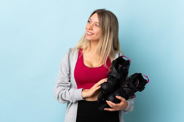 Молодая блондинка женщина, держащая роликовые коньки, изолированные на розовой стене, глядя в сторону