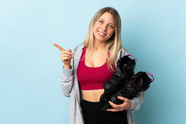 横に指を指しているピンクの壁に分離されたローラースケートを保持している若いブロンドの女性