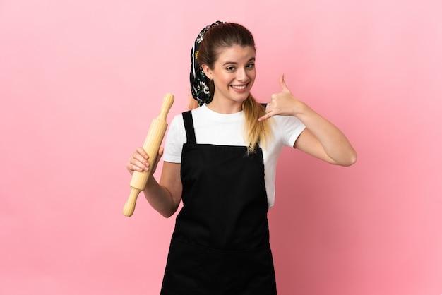電話のジェスチャーを作るピンクの壁に分離された麺棒を保持している若いブロンドの女性。コールバックサイン