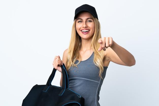 Молодая белокурая женщина, держащая спортивную сумку над изолированной белой стеной, уверенно указывает пальцем на вас