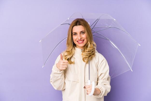 分離された傘を保持している若いブロンドの女性分離された傘を保持している若いブロンドの女性