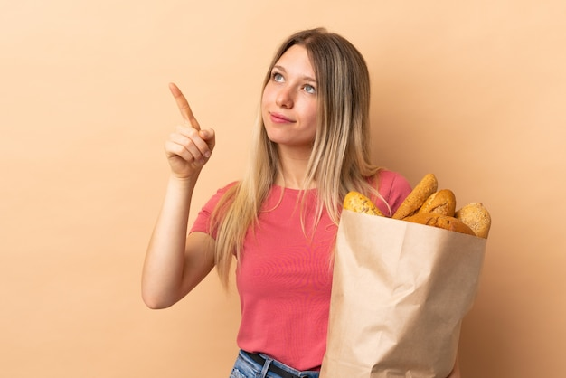 Young blonde woman holding a bag full of breads isolated on beige wall touching on transparent screen