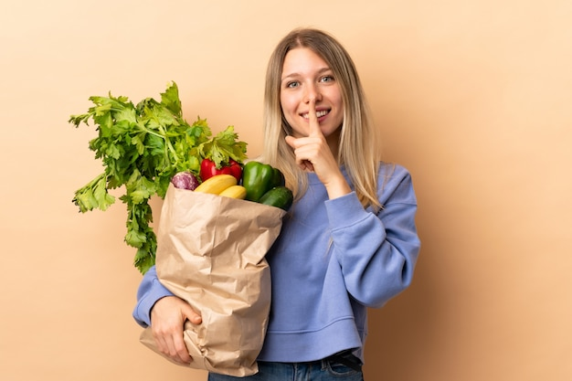 Young blonde woman holding a bag full of vegetables over isolated wall doing silence gesture