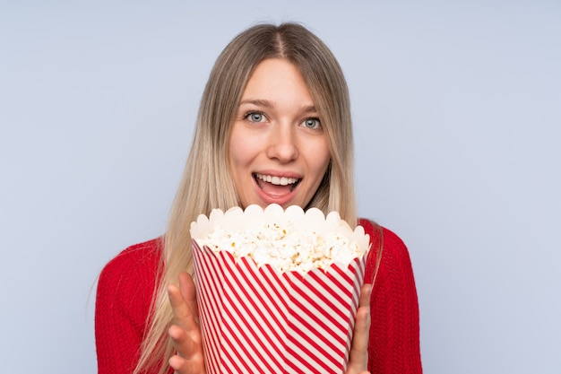 Young blonde woman holding a big bucket of popcorns