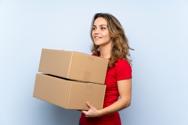 Young blonde woman holding a box to move it to another site