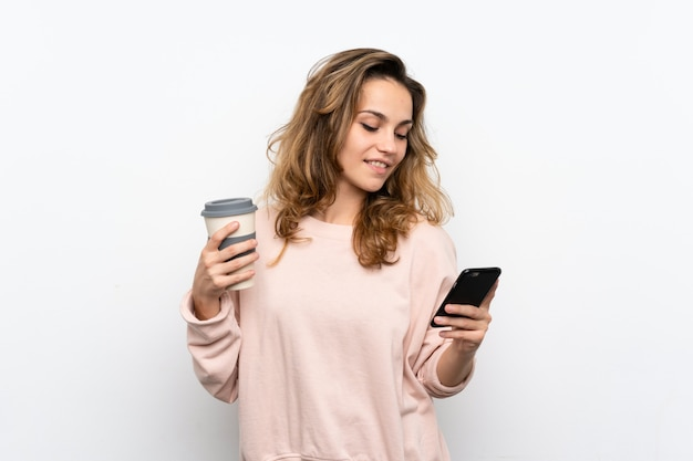 Young blonde woman holding coffee to take away and a mobile