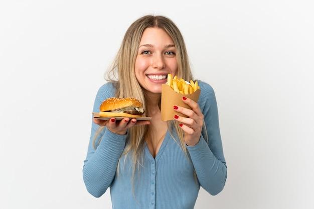 孤立した背景の上に揚げチップスとチーズバーガーを保持している若いブロンドの女性
