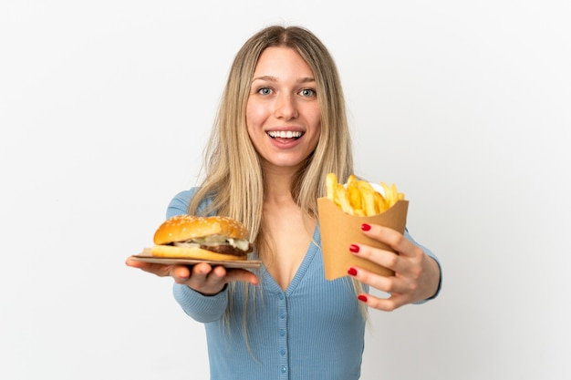 Young blonde woman holding fried chips and cheeseburger over isolated background