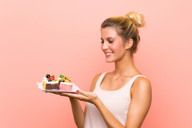 Young blonde woman holding lots of different mini cakes with surprise facial expression