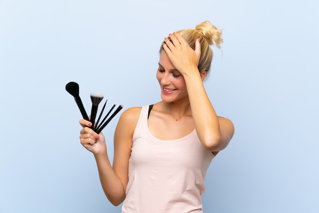 Young blonde woman holding lots of makeup brush has realized something and intending the solution