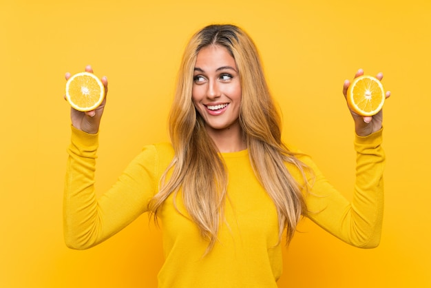 Young blonde woman holding an orange over yellow wall