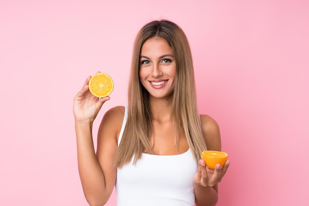 Young blonde woman holding an orange