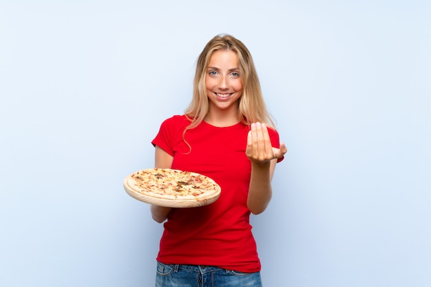 Young blonde woman holding a pizza over  blue wall inviting to come with hand. happy that you came