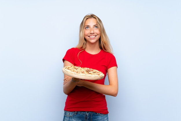 Young blonde woman holding a pizza over isolated blue wall looking up while smiling