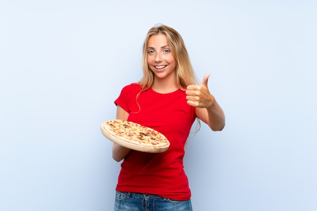 Young blonde woman holding a pizza over isolated blue wall with thumbs up because something good has happened