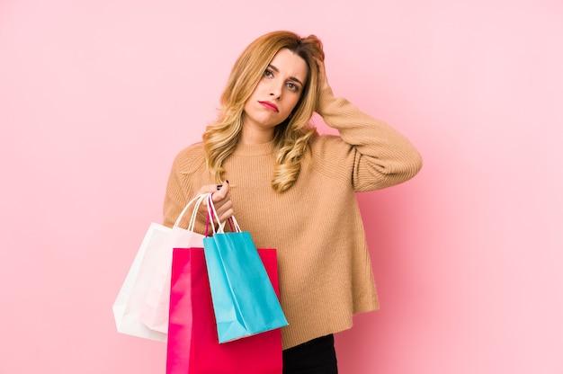Молодая блондинка женщина, держащая изолированные сумки для покупок в шоке, она вспомнила важную встречу.