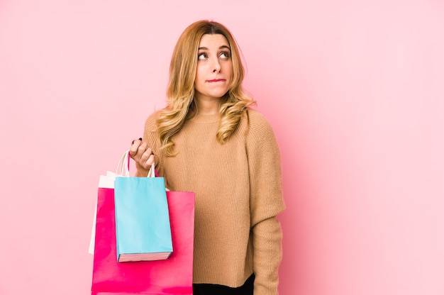 Young blonde woman holding shopping bags isolated confused, feels doubtful and unsure.