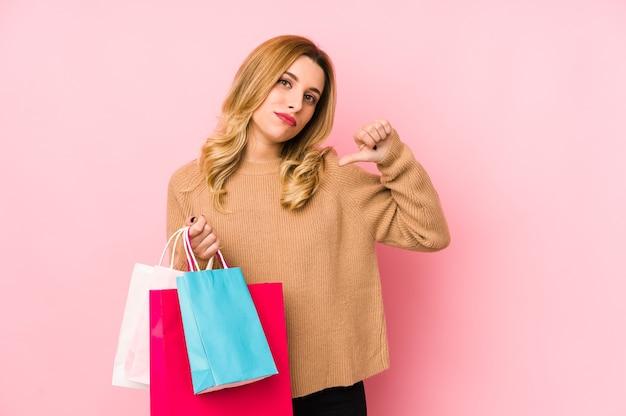 孤立した買い物袋を保持している若いブロンドの女性は、従うべき例を誇りに思い、自信を持っています。