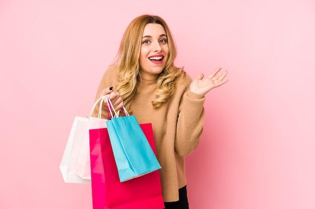 買い物袋を持って若いブロンドの女性は、嬉しい驚きを受けて興奮し、手を上げて分離しました。